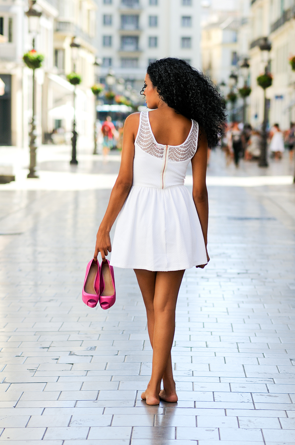 Portrait of a young black woman, afro hairstyle, walking barefoot on a commercial street